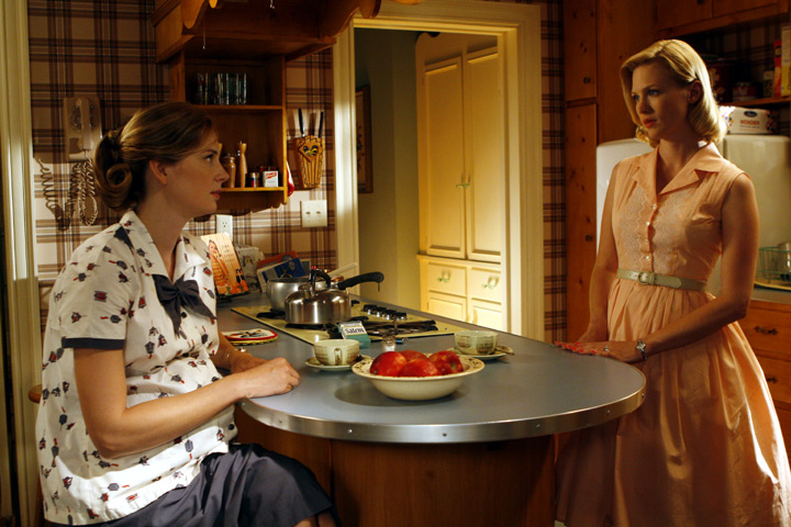 two women in kitchen with plaid wallpaper